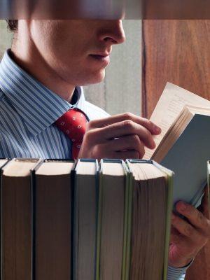 Homem lendo livros sobre empreendedorismo